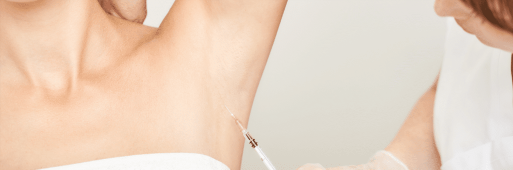 Underarm injection at spa salon. Doctor hands. Female patient.